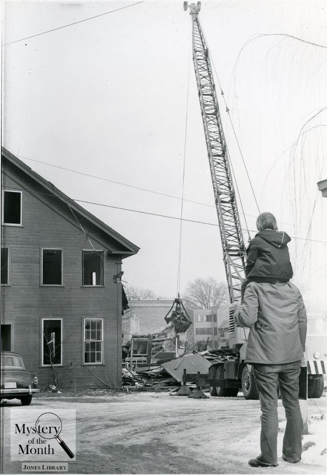 A man and boy watch as a building is demolished
