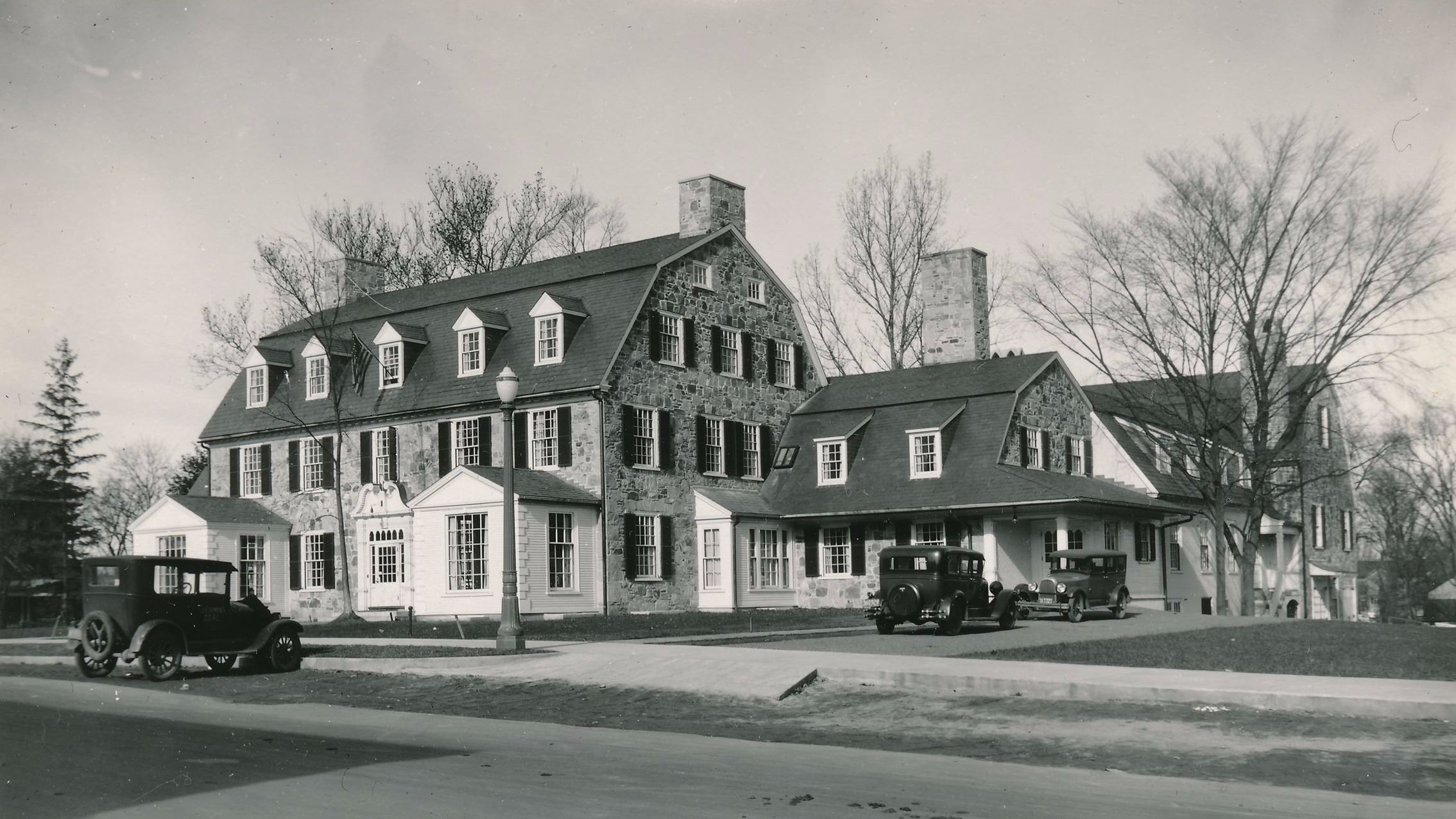Jones Library exterior in 1932 with cars parked outside.